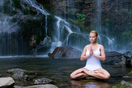 Beautiful young woman doing yoga in a water pool near waterfall photo