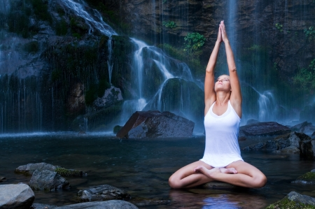 puro: Joven y bella mujer haciendo yoga de la posición de loto en una piscina de agua cerca de cascada  Foto de archivo