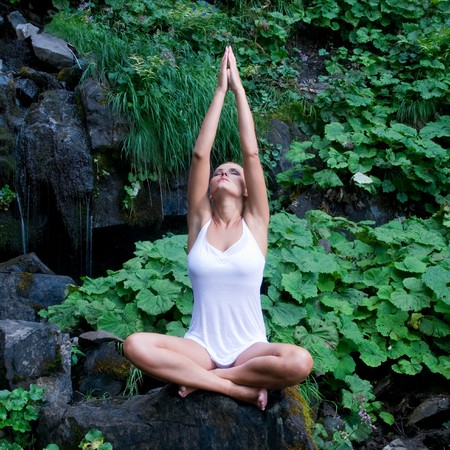 Beautiful young woman doing yoga in lotus position near waterfall and green leaves Reklamní fotografie
