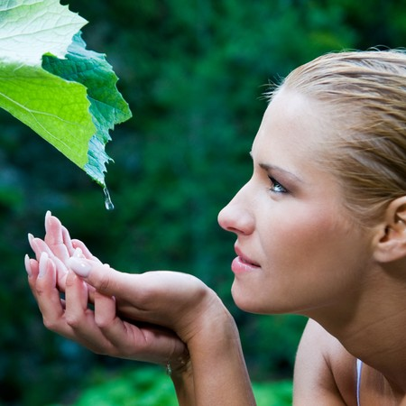 Beautiful young woman take a drop of clear water from a leaf in the nature. Symbol of purity, body care and nature harmony photo