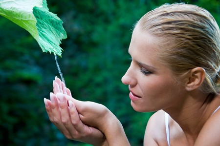 dews: Beatiful young woman with open hands take fresh flowing water from a green leaf in the nature. Symbol of harmony and body care