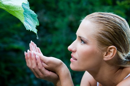 Beatiful young woman with open hands take fresh water drops from a green leaf in the nature. Symbol of harmony and body care photo