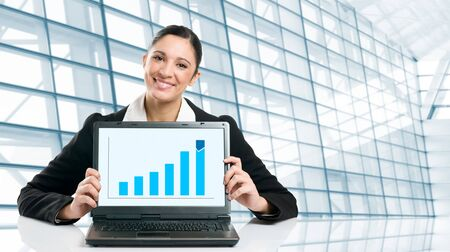 Young business woman displaying successful growing graph on her laptop in a modern office photo