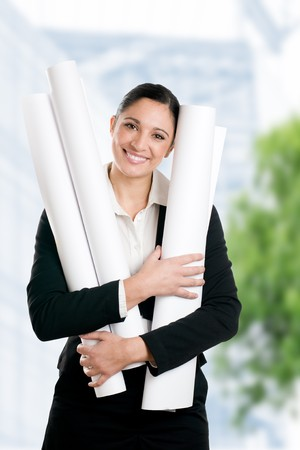 Satisfied young woman architect with her plans looking at camera outdoor in the city Stock Photo - 8235103