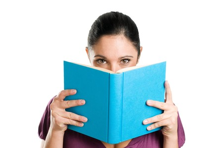 Beautiful young casual woman hiding herself behind a book isolated on white background Stock Photo
