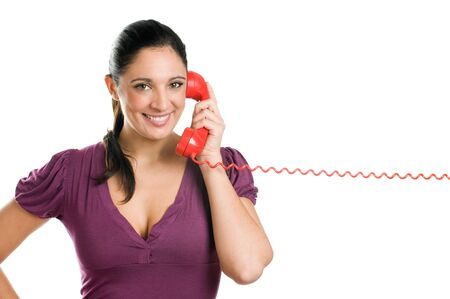 cord: Young casual woman holding a red receiver and smiling at the phone call