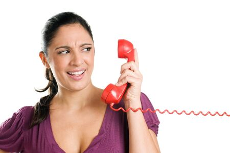 telephonist: Surprised young woman looking at the receiver with astonishment isolated on white background Stock Photo