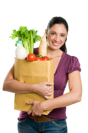 shopper: Young woman holding a grocery bag full of fresh and healthy food isolated on white background
