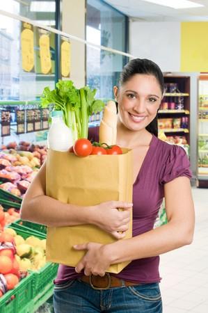 bolsa supermercado: Joven sosteniendo una bolsa de supermercado llena de comida fresca y saludable en un supermercado