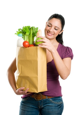 sac �picerie: Young woman holding a grocery bag and put in it a fresh apple isolated on white background