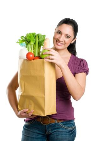 bolsa supermercado: Joven sosteniendo una bolsa de supermercado y poner en ella una manzana fresca aislados sobre fondo blanco