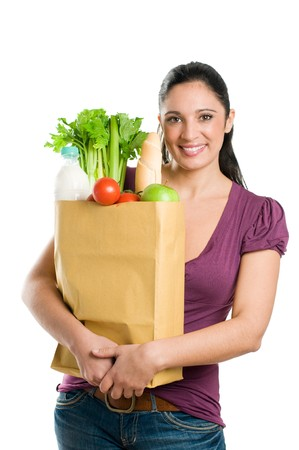 shoppers: Young woman holding a grocery bag full of fresh and healthy food isolated on white background