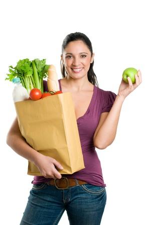 bolsa supermercado: Joven sosteniendo una bolsa de supermercado y mostrando una manzana fresca aislada sobre fondo blanco