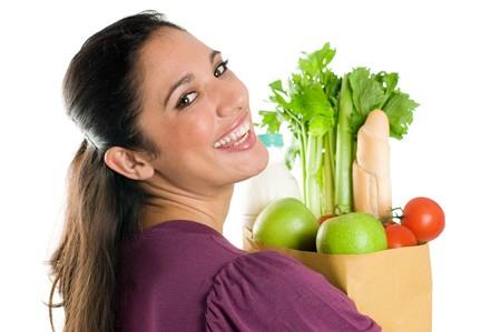 chicas de compras: Joven sosteniendo una bolsa de supermercado llena de alimentos frescos y saludables aislados sobre fondo blanco