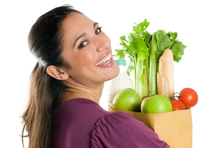hypermarket: Young woman holding a grocery bag full of fresh and healthy food isolated on white background