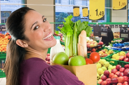 grocery shopping: Young woman holding a grocery bag full of fresh and healthy food inside a supermarket