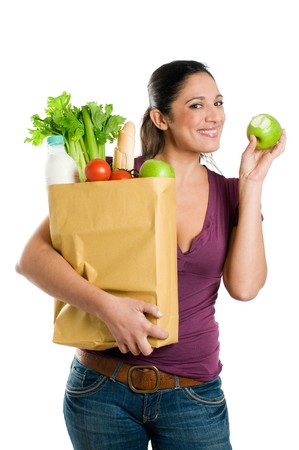 Young woman holding a grocery bag and eating a fresh apple isolated on white background photo