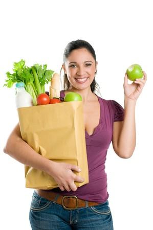 bolsa supermercado: Joven sosteniendo una bolsa de supermercado y comer una manzana fresca aislada sobre fondo blanco  Foto de archivo