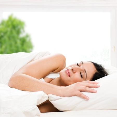 łóżko: PiÄ™kne mÅ'oda kobieta spanie na łóżku w jej Sypialnia w domu w rano