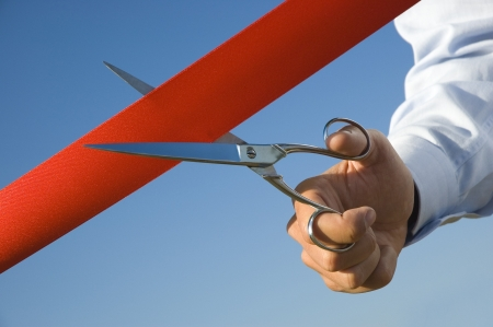 unveiling: Red ribbon cutting with a pair of scissors for the inauguration of the new business activity