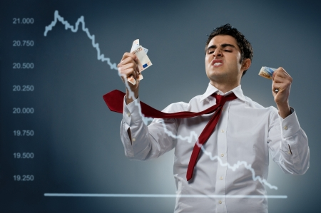 stock market crash: Young businessman getting mad behind a declining share. Recession and crisis concept!