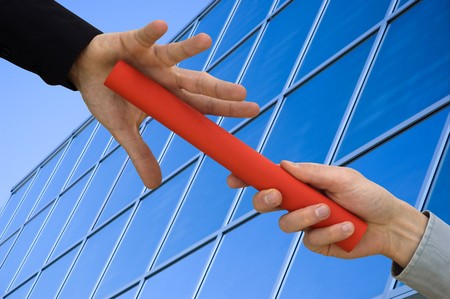 One businessman passing a red baton to another businessman over blue office building. Symbol of teamwork, helping and partnership. photo