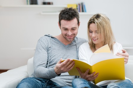 reading room: Young couple reading together a magazine in their living room at home Stock Photo