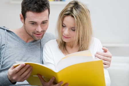 Young couple reading together a magazine in their living room at home Stock Photo - 8235541