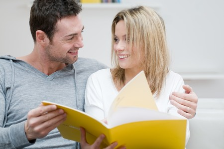 Young couple reading together a magazine and looking each other in their living room at home photo