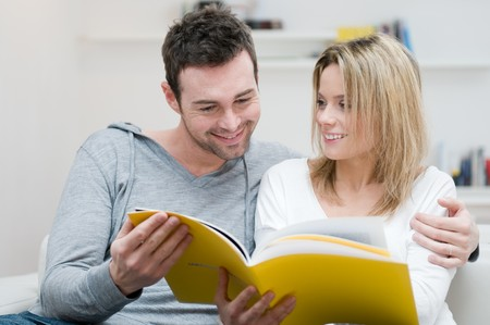 Young couple reading together a magazine in their living room at home photo