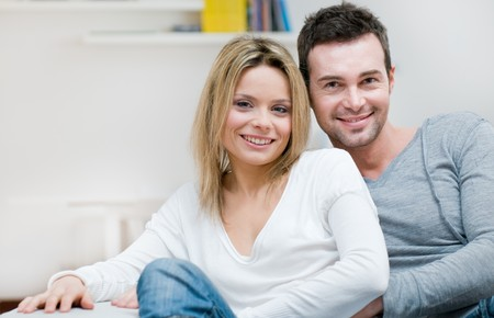 Young serene couple looking at camera together in their living room at home photo