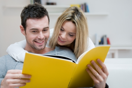 adult magazines: Young couple reading together a magazine in their living room at home Stock Photo
