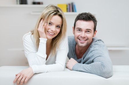 Young happy couple smiling together at camera in their home photo