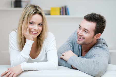 Young happy couple smiling with joy at camera in their home photo