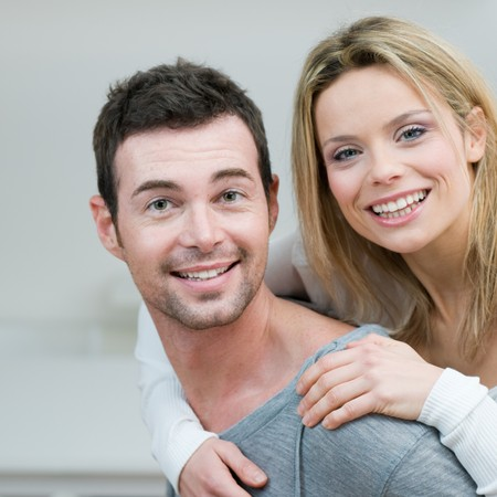 Young couple piggybacking and have fun at home photo