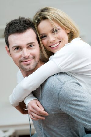 Young couple piggybacking and have fun at home Stock Photo - 8235583