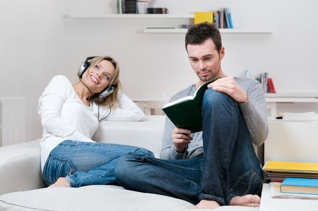 Young couple relaxing on the couch in their living room at home Stock Photo - 8235543
