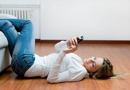 Young beautiful woman text messaging on mobile while relaxing on the floor photo
