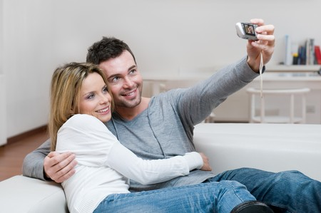 Young couple taking a self portrait with digital camera at home photo