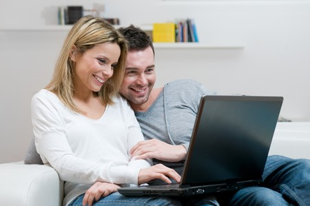 Young couple relaxing on the couch with laptop in their living room at home photo