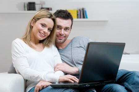 net surfing: Giovane coppia felice navigazione in rete con loro laptop a casa, copiare lo spazio