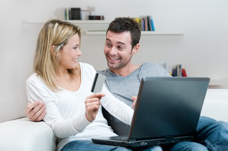 Young smiling couple making shopping online with credit card at home Stock Photo - 8235490