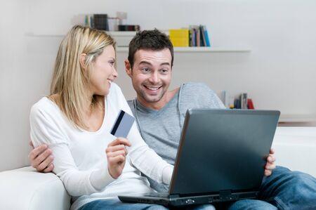 Jonge lachende paar maken online winkelen met credit card thuis