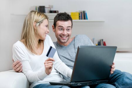 Young smiling couple making shopping online with credit card at home photo