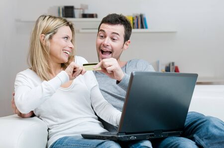 Young couple contend for a credit card for internet shopping with fun at home photo