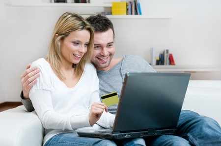 Young couple doing shopping in internet with credit card at home photo