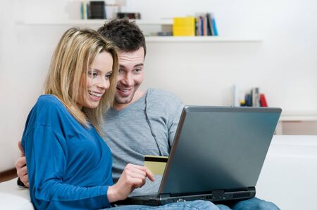 Young couple making shopping online with credit card at home Stock Photo - 8235491