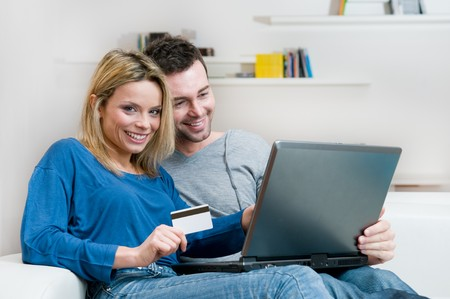 Young couple making shopping online with credit card and laptop at home photo