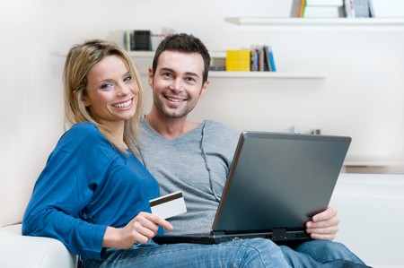 Smiling young couple making shopping online with credit card and laptop at home photo