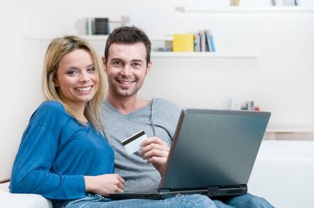 card making: Smiling young couple making shopping online with credit card and laptop at home Stock Photo
